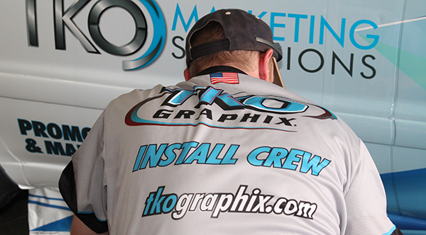 TKO Graohix installer applying a decal to a van