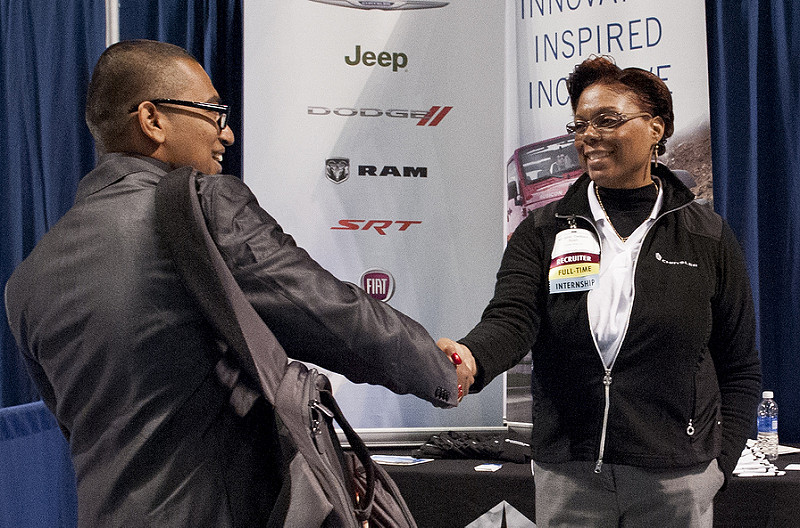 Two people shaking hands in front of a trade show banner