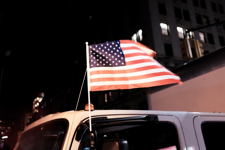 American flag attached to a truck window flapping in the wind