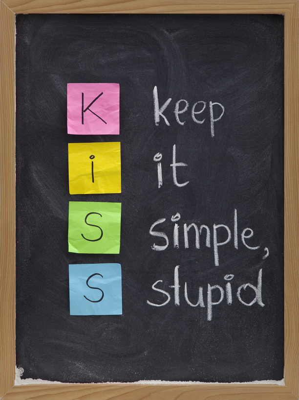 KISS keep it simple, stupid - design principle presented with sticky notes and white chalk handwriting on blackboard