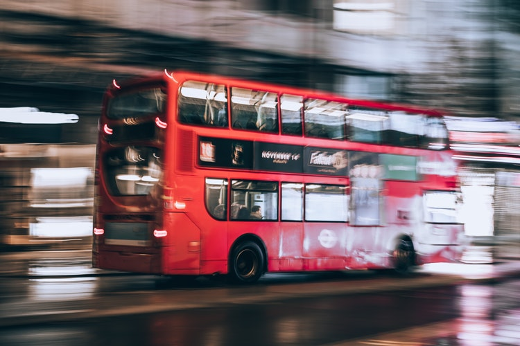 A red double decker bus driving on a road