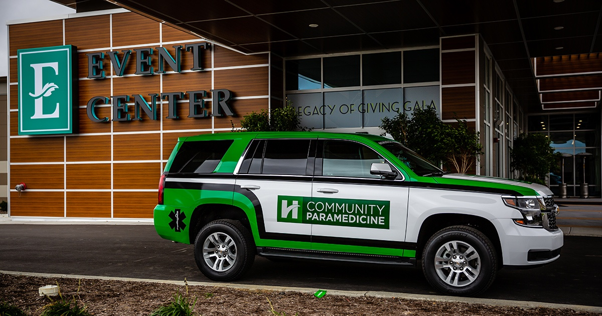 Chevy SUV parked in front of Event Center with Green and White Vehicle Graphics