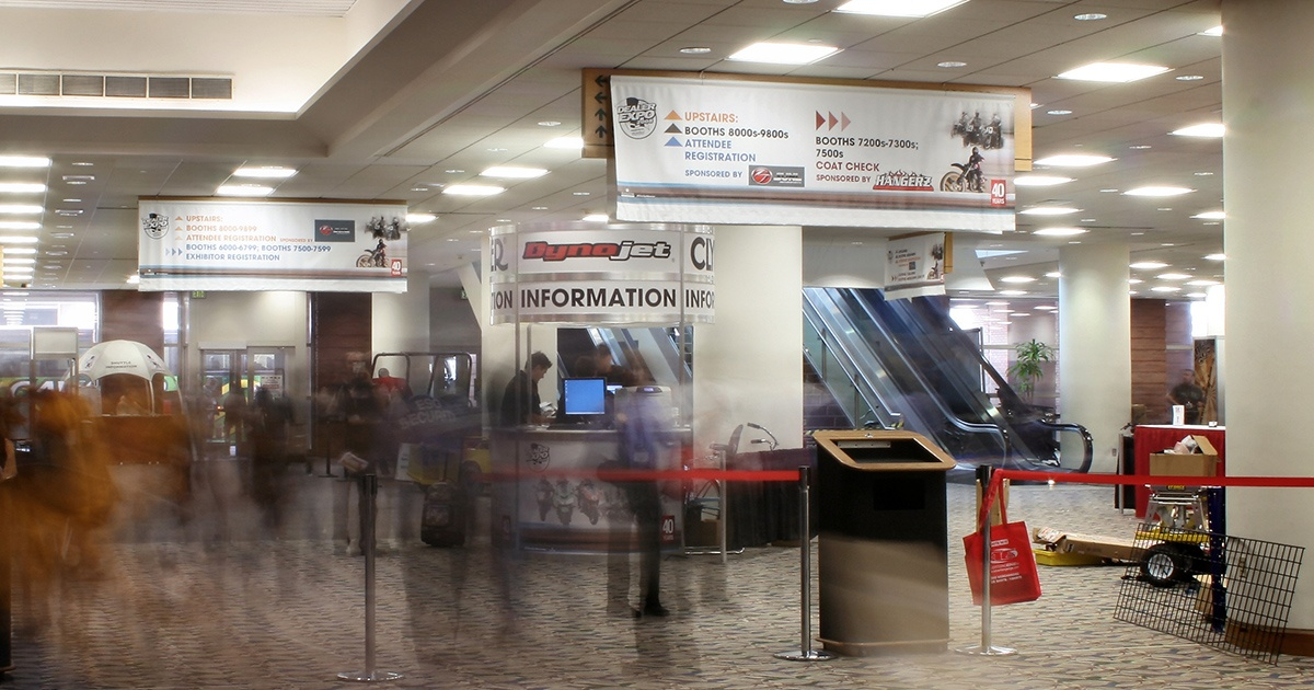 Large Directional Banners Hanging from Ceiling at Busy Trade Show